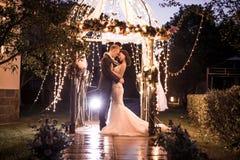 Elegant couple embracing in illuminated gazebo at night Stock Photos