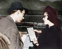 Elegant couple at a horse race looking at a program stock photos