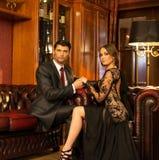 Elegant couple in luxury cabinet. Elegant couple in formal dress in luxury cabinet interior royalty free stock image