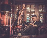 Elegant couple in luxury cabinet interior royalty free stock image