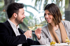 Elegant Couple making toast with white wine in restaurant. Close up of young handsome Couple sharing special moment white wine in restaurant Royalty Free Stock Photo