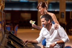 Elegant couple playing the slot machine Stock Image
