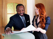 Elegant couple - red headed woman an black man. Business companions - red head businesswoman  and black american businessman smiling Royalty Free Stock Images