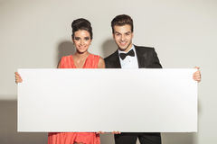 Elegant couple smiling while holding a white board Royalty Free Stock Photography