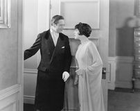 Elegant couple standing in the doorway. (All persons depicted are no longer living and no estate exists. Supplier grants that there will be no model release stock photo
