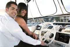 Elegant couple in a yacht laughing. Elegant couple in a control yacht laughing Royalty Free Stock Photography