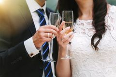 An elegant couple of young people. An elegant couple of young newlyweds is being checked by glasses with champagne in the rays of the sun Stock Photo