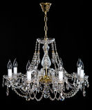 Elegant crystal strass chandelier with eight lamps. Golden elegant crystal strass chandelier with eight lamps. Diamond strass chandelier on black background Stock Photography