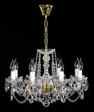 Elegant crystal strass chandelier with eight lamps. Golden elegant crystal strass chandelier with eight lamps. Diamond strass chandelier on black background Stock Image
