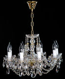 Elegant crystal strass chandelier with eight lamps. Golden elegant crystal strass chandelier with eight lamps. Diamond strass chandelier on black background Stock Images
