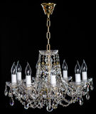 Elegant crystal strass chandelier with eight lamps. Golden elegant crystal strass chandelier with eight lamps. Diamond strass chandelier on black background Stock Photos