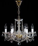 Elegant crystal strass chandelier with six lamps. Golden elegant crystal strass chandelier with six lamps. Diamond strass chandelier on black background Stock Image