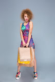 Elegant curly young woman with many shopping bags Stock Image