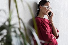 Elegant cute girl is having enjoyable communication. Pleasant conversation. Cheerful fascinating young asian woman is talking on modern smartphone while leaning royalty free stock photography