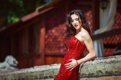 Elegant dam i röd klänning utanför Arkivfoton