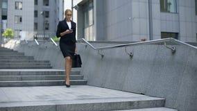 Elegant dam som går ner trappa och kontrollerar post på smartphonen, upptagen livsstil lager videofilmer