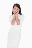 Elegant dark haired model wearing white dress touching her face Stock Photo