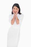 Elegant dark haired model wearing white dress touching her face Stock Photo