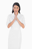 Elegant dark haired model with white dress joining hands Stock Images