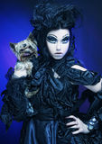Elegant dark queen with little dog Stock Photo