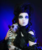 Elegant dark queen with little dog Royalty Free Stock Image