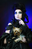 Elegant dark queen with little dog Royalty Free Stock Images