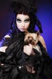 Elegant dark queen with little dog over dark background Royalty Free Stock Photos