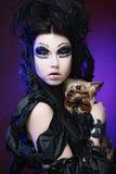 Elegant dark queen with little dog over dark background Stock Photo