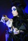 Elegant dark queen with little dog over dark background Stock Image