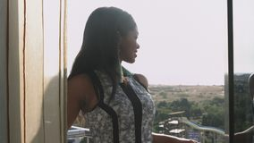 An elegant dark-skinned young girl stands on the balcony and admires the view