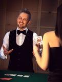 Elegant dealer smiling girls playing poker. In a casino Stock Image