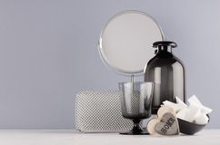 Elegant decor dressing table in minimalist style - black vase, glass, cosmetic accessories, mirror, wooden heart on grey wall. Elegant decor dressing table in stock photos