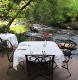 Elegant Dining beside a Creek. A beautiful setting for a romantic dinner on a creekside deck stock images