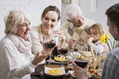 Elegant dinner of a multigenerational family. With a grandmother raising her glass in a toast royalty free stock photography