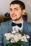 Elegant dressed handsome young groom holding wedding bouquet of white roses Royalty Free Stock Image