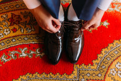 Elegant dressed man tying stylish leather shoes indoors standing on fancy oriental style carpet.  Royalty Free Stock Photography