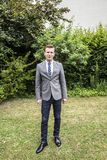 Elegant dressed teenage boy poses in the garden Royalty Free Stock Images