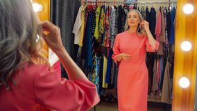 Elegant elderly grey haired woman is trying on earrings talking to the seller in store in front of the mirror. Beautiful elegant elderly grey haired woman in stock footage