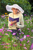 Elegant elderly lady reading in her garden Royalty Free Stock Images
