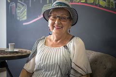 Elegant elderly woman sitting in the cafe place royalty free stock photos