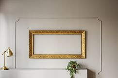 Elegant, empty golden frame inside molding on a gray wall of a stylish living room interior with lamp and a plant. Real photo. Elegant, empty golden frame stock photo