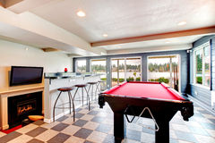 Elegant entertainment room with pool, bar and fireplace Royalty Free Stock Images