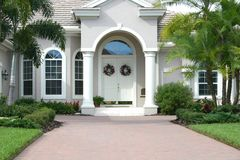 Elegant Entrance to Beautiful Home. With double doors,columns, tropical landscaping and wide brick driveway stock photos