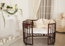 Elegant expensive bed for newborn baby. Luxury decorations of apartments.  Royalty Free Stock Images