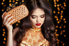 Elegant fashion brunette woman in gold. Wavy hair style. Red lip. S Makeup. Healthy shiny hairstyle. girl model in golden dress with trendy clutch bag stock image