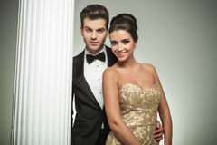 Elegant fashion couple smiling together near column. In studio Stock Photography