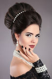 Elegant fashion jewelry woman portrait. Brunette lady with makeup and hairstyle, pearls accessories set posing isolated on studio royalty free stock photos