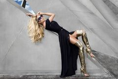 Elegant fashion model in a beautiful black dress and golden long shoes Royalty Free Stock Image