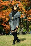 Elegant fashion model posing pretty in the park. Elegant fashion model posing pretty in the park with colorful autumn trees on the background Royalty Free Stock Photos