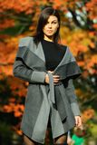 Elegant fashion model posing pretty in the park. Elegant fashion model posing pretty in the park with colorful autumn trees on the background Stock Image